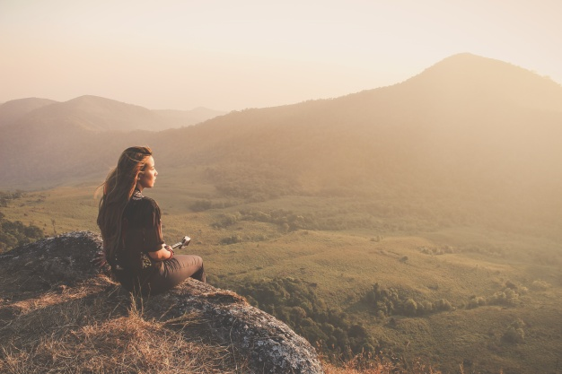 woman-sitting-on-the-floor-looking-at-sunset_1253-217